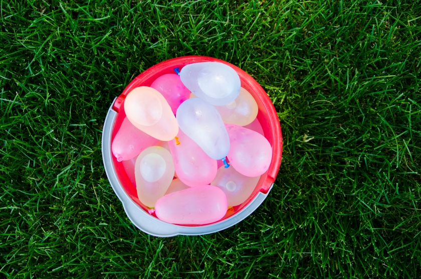 Water Balloons in Bucket on Grass